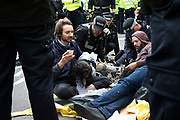 Police cut free and remove the last three protesters who are locked on as they try to clear climate change activists from the Extinction Rebellion group at Oxford Street near to the Marble Arch camp in protest that the government is not doing enough to avoid catastrophic climate change and to demand the government take radical action to save the planet, on 24th April 2019 in London, England, United Kingdom. Extinction Rebellion is a climate change group started in 2018 and has gained a huge following of people committed to peaceful protests.