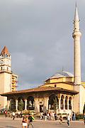 The Ethem Bey Beu Mosque. People and cars on the street in front. The Tirana Main Central Square, Skanderbeg Skanderburg Square. Tirana capital. Albania, Balkan, Europe.