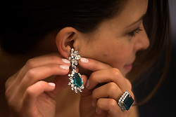 © Licensed to London News Pictures. 10/04/2013. London, UK. A model wears a pair of emerald and diamond earclips and an emerald and diamond ring. Sotheby's Geneva will offer 23 outstanding jewels from the collection of the legendary actress Gina Lollobrigida in its Magnificent Jewels and Noble Jewels Sale on 14 May 2013..Photo credit : Peter Kollanyi/LNP