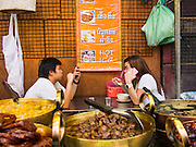 11 SEPTEMBER 2013 - BANGKOK, THAILAND:  Women chat and use their smart phones while they eat Thai desert soups at a street stall in the Chinatown section of Bangkok. Thailand in general, and Bangkok in particular, has a vibrant tradition of street food and eating on the run. In recent years, Bangkok's street food has become something of an international landmark and is being written about in glossy travel magazines and in the pages of the New York Times.        PHOTO BY JACK KURTZ