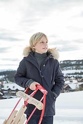 boy holding a sled