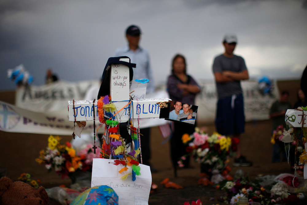 """People stand in the rain looking over a memorial to the theater-goers killed in the mass shooting July 20, 2012 in Aurora, Colorado July 27, 2012. The third funeral in as many days took place Friday in this Denver suburb for victims of last week's deadly shooting rampage at a midnight screening of the latest """"Batman"""" film. REUTERS/Rick Wilking (UNITED STATES)"""