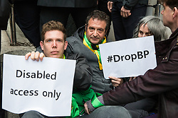 London, UK. 10 June, 2019. Comedian, writer and actor Mark Thomas joins activists from BP or not BP? in blocking access to the National Portrait Gallery in protest against BP's sponsorship of the BP Portrait Award. The energy company has sponsored the National Portrait Gallery's award for 30 years, but its high-profile involvement is attracting widespread criticism due to the intensifying focus on environmental issues. A number of artists, including previous award winners such as Wim Heldens and Craig Wiley, have called on the gallery to end its sponsorship by BP.