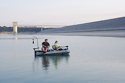 Father and daughter fishing on Lake Buchanan, one of the Highland Lakes formed by the Colorado River during low water drought conditions.