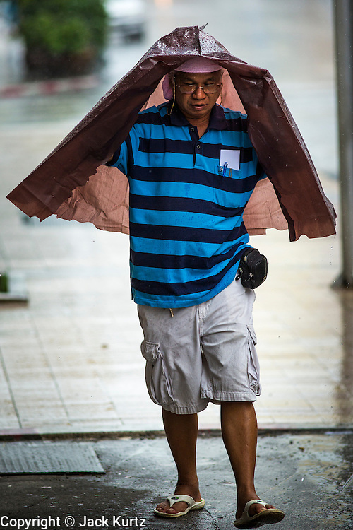 23 OCTOBER 2012 - HAT YAI, THAILAND:      A man tries to stay dry during a rainy season squall in Hat Yai, Thailand. Hat Yai is the largest in southern Thailand. It is an important commercial center and tourist destination. It is especially popular with Malaysian, Singaporean and Chinese tourists.        PHOTO BY JACK KURTZ