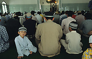 Batak Muslims in prayer at Mosque..Batak Indigenous Christian people living on Samosir Island and nearby Lake Toba in Indonesia. There are some 6 million Christian Batak in Indonesia, the world's largest Muslim country of 237 million people, which has more Muslims than any other in the world. Though it has a long history of religious tolerance, a small extremist fringe of Muslims have been more vocal and violent towards Christians in recent years. ..Batak religion is found among the Batak societies around Lake Toba in north Sumatra. It is ethnically diverse, syncretic, liable to change, and linked with village organisations and the monotheistic Indonesian culture. Toba Batak houses are boat-shaped with intricately carved gables and upsweeping roof ridges, and Karo Batak houses rise up in tiers. Both are built on piles and are derived from an ancient Dong-Son model. The gable ends of traditional houses, Rumah Bolon or Jabu, are richly decorated with the cosmic serpent Naga Padoha carved in wood or in mosaic, lizards, double spirals, female breasts, and the head of the singa, a monster with protruding eyes that is part human, part water buffalo, and part crocodile or lizard. The layout of the village symbolises the Batak cosmos. They cultivate irrigated rice and vegetables. Irrigated rice cultivation can support a large population, and the Toba and the Karo live in densely clustered villages, which are limited to around ten homes to save farming land. The kinship system is based on marriage alliances linking lineages of patrilineal clans called marga. In the 1820's Islam came to the southern Angkola and Mandailing homelands, and in the 1850's and 1860's Christianity arrived in the Angkola and Toba region with Dutch missionaries and the German Rheinische Mission Gesellschaft. The first German missionary caused the Dutch to stop Batak communal sacrificial rituals and music, which was a major blow to the traditional religion. Dutch colonial policy favoured Christian vill