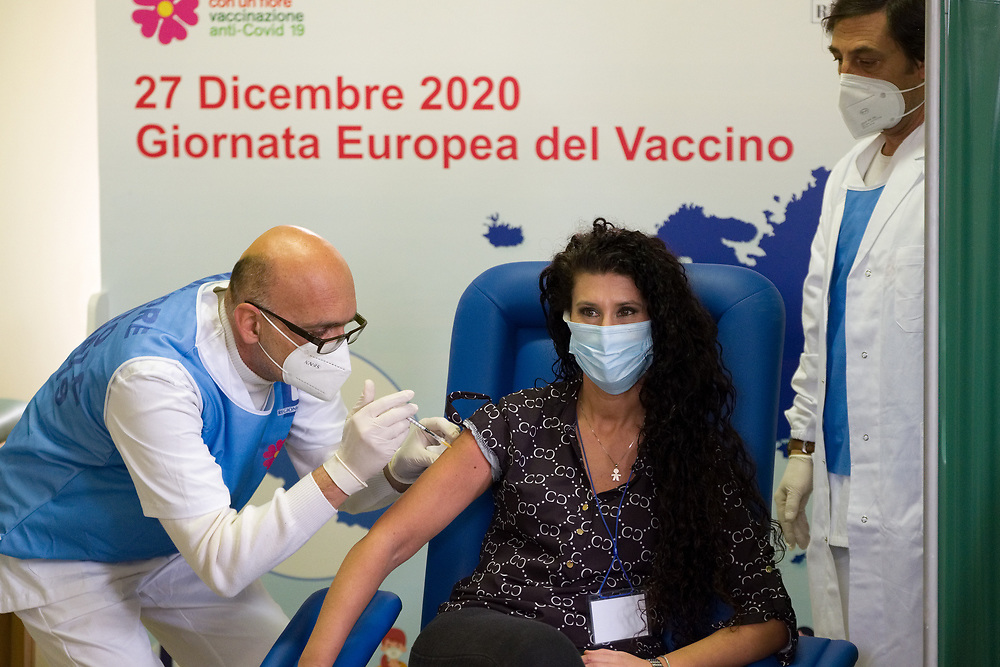 A woman wearing a protective face mask against the spread of COVID-19 coronavirus receives a dose of the Pfizer-BioNTech COVID-19 vaccine at Frullone nursing home in Naples, southern Italy, on December 27, 2020. Today is started the vaccination campaign simultaneously throughout Europe.