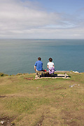 A walking couple rest on a bench at Morte Point on the North Devon Coast. Gazing out to see in the direction of South Wales straight ahead or out to the Atlantic to the right, they sit in peace on a calm summers day. Green grasses carpet the rocks on this clifftop location, a favourite of coastal trekkers and outdoor enthusiasts. Owned by the National Trust, Morte Point is a spectacular headland on the North Devon coast behind the village of Mortehoe near Woolacombe. The treacherous reefs and strong currents at the point, have caused numerous shipwrecks.