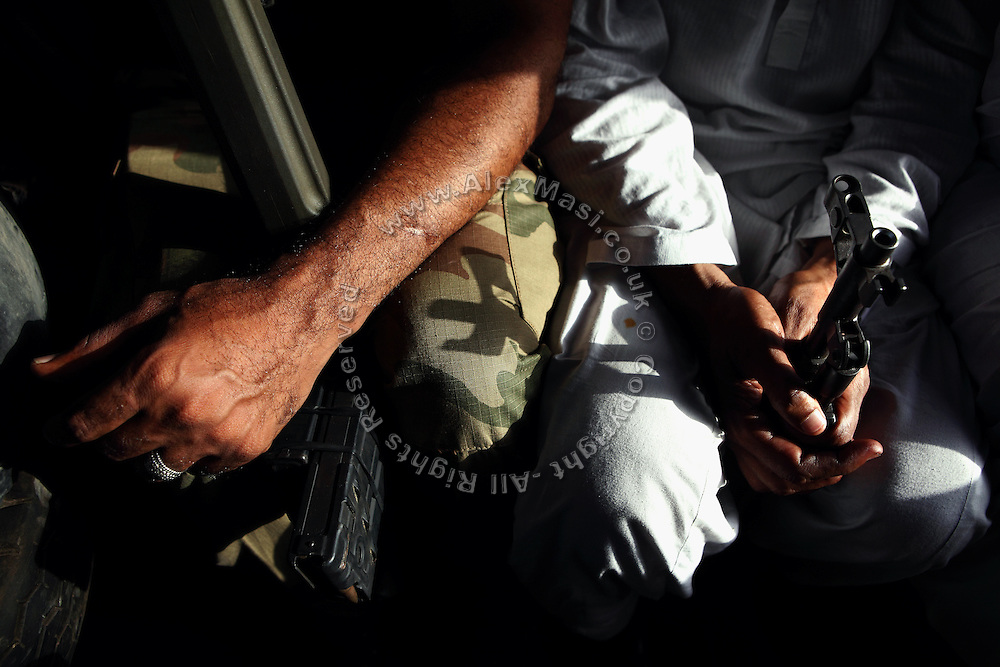 Armed members of the AVCC, (Anti-Violence Crime Cell) a special police unit mostly involved in anti-terrorism operations and kidnap cases in the city of Karachi, are sitting in their vehicle on the way to a raid on the outskirts of the city while searching for a kidnap suspect.