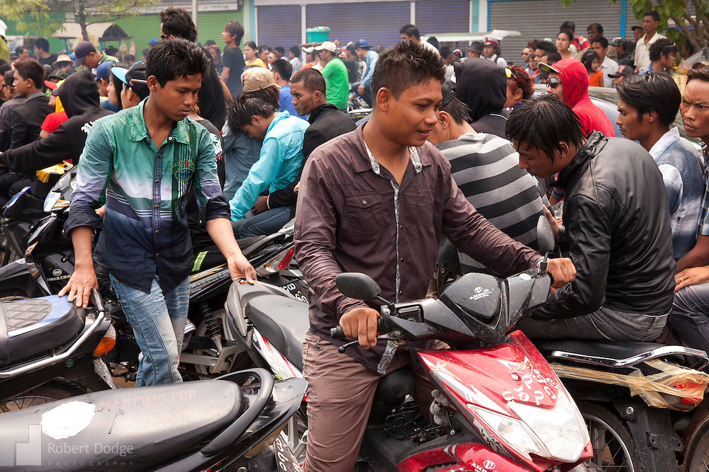 andalay, Myanmar- April 14, 2013: Traffic came to a standstill during Myanmar's Thingyan Water Festival. Thingyan is held in April, one of the hottest months of the year in Myanmar. The water festival marks the country's New Year celebration and the festival includes lots of drinking, singing, dancing and theater. Wherever you are you are likely to get doused with water as the Burmese see this as a cleansing of the previous year's sins and bad luck and a blessing for good luck and prosperity in the year ahead. In the major cities of Mandalay and Yangon, large platforms are erected along major roadways and are equipped with high powered water hoses. The platforms, sponsored by large corporate donors, also have dance stages and play the latest pop and hip hop music. Thousands of residents pour into the streets by foot, motorbike and flatbed truck to get hosed under the platforms while they drink and dance. Many of the young celebrants wear their best clubbing clothes. And many of the party goers are men, having left their wives and girlfriends at home.