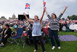 © Licensed to London News Pictures.22/08/15<br /> Castle Howard, North Yorkshire, UK. <br /> <br /> Two women dance and wave flags as hundreds of people attend the 25th anniversary of the Castle Howard Proms event near York. The theme of the event this year is a commemoration of the 75th anniversary of the Battle of Britain and the 70th anniversary of VE day and brings an evening of classic musical favourites celebrating Britishness to the lawns of Castle Howard.<br /> <br /> Photo credit : Ian Forsyth/LNP