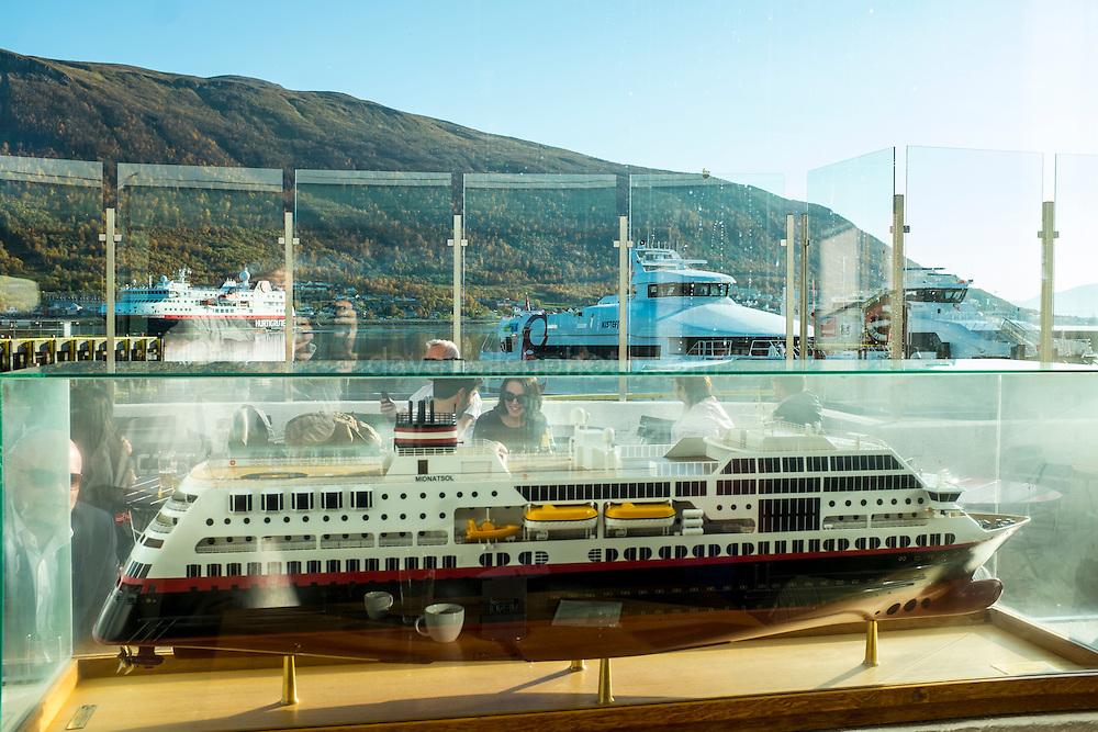 Model Hurtigruten ship, with real ship arriving outside. Tromso, Norway