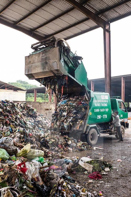 Garbage trucks unloading rubbish at the compost plant of Cau Dien, a commune near Hanoi, Vietnam, Southeast Asia