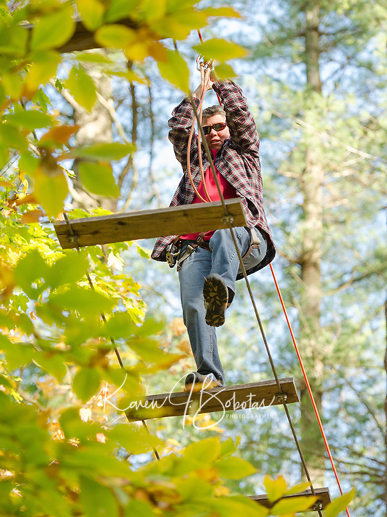 Maggie Clarke makes her way across the wide planks during the Wounded Warrior programs outing at the Tree Top Adventure Ropes Course at Gunstock on Monday afternoon.  (Karen Bobotas/for the Laconia Daily Sun)