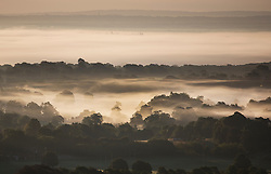 © Licensed to London News Pictures. 23/09/2016. Dorking, UK.  Early morning mist lies over Surrey as the sunrises - seen from Box Hill on the second day of Autumn. Photo credit: Peter Macdiarmid/LNP