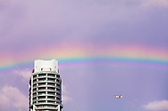 A rainbow and an aircraft pass near a Miami condo building. WATERMARKS WILL NOT APPEAR ON PRINTS OR LICENSED IMAGES.