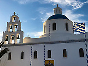 Ekklisia (church) Agios Onoufrios in late afternoon with greek flag blowing in the wind, Oia, Santorini