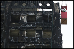 August 14, 2017 - London, United Kingdom - Workmen in a crane outside the Grenfell residential tower block in West London which  engulfed by a fire two months ago causing at least 80 deaths and over 70 injuries. Up to 200 survivors are still living in hotels and have resorted to searching for new homes themselves out of frustration at the council's rehousing efforts. (Credit Image: © Dinendra Haria/i-Images via ZUMA Press)