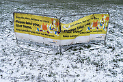 Lambeth councils banner warning against littering, a landscape in a light covering of snow in Brockwell Park, a public space in SE24, south London, on 8th February 2021, in London, England.