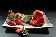 A white plate of cut fruit Strawberries, Kiwi and Apple on black background