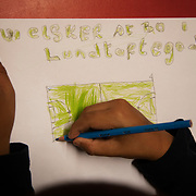 """A child makes a drawing of the footbal pitch saying """" We love Lundtoftegade"""".  Lundtoftegade is a housing estate in the heart of Copenhagen. The estate has been on the controversial Ghetto List for years but wastaken off 1st of December 2020. The Ghetto List is based on the Ghetto Law introduced by the Danish Govenrment in 2018. In 2020 a huge campaign was launched to raise 50.000 signatures demanding the Danish Parliament to reconsider the law and to abolish it. Part of the campaign was the national portrait poster campaign 'We ARE the mixed city'. More than 100 local residents in joined the campaign and were photographed in a small make shift studio set up in Lundtoftegade. These images are fragments of life in and around Lundtoftegade 2020."""