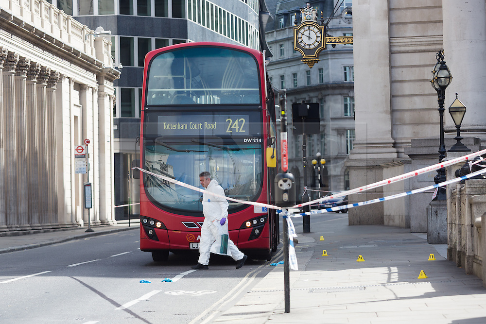 © Licensed to London News Pictures. 24/07/2016. LONDON, UK.  A forensic officer gathers evidence at the scene. A 26 year old man was stabbed outside Bank Tube station in Threadneedle Street near the Bank of England in the early hours of this morning. The man is then reported to have staggered onto the N242 bus, horrifying passengers. Ambulance and police emergency services were then called.  Photo credit: Vickie Flores/LNP