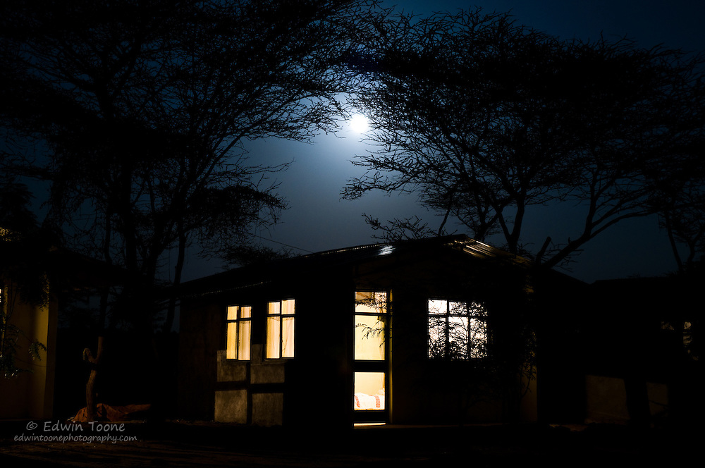 A bright moon shines over a cabin in a camp ground in the Omo River Valley, Ethiopia.