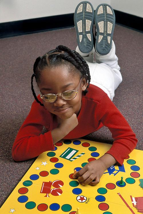 Austin, Texas:  Five (5) year old African-American girl plays children's board game. ©Bob Daemmrich /