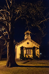 The old yellow school house in Middletown, Rhode Island is well lighted at night.