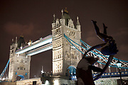 Night scene of Tower Bridge in London on a cold winter evening. The well known David Wynne sculpture 'Girl with a Dolphin' (1973) stands on the bank of the Thames, to the north-east side.