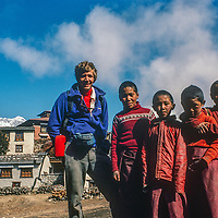 Gordon Wiltsie poses with young Tibetan Buddhist monks in front of Mount Everest and Tengboche Monastery in the Khumbu region of Nepal in 1986, before the old monastery  was destroyed and rebuilt after an electrical fire in 1989.