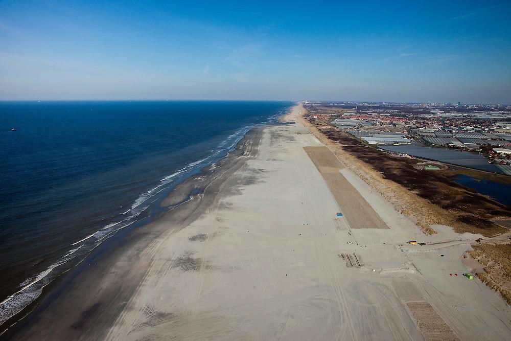 Nederland, Zuid-Holland, 's-Gravenzande, 18-03-2009; Versterking van de kust van Delfland tussen Ter Heijde en 's-Gravenzande door middel van zandsuppletie. Het strand onder in beeld is breder, hier is al gesuppleerd, verder naar horizon moet er nog zand opgespoten worden. Het strand is extra breed gemaakt om een tweede duinenrij met duinvallei te maken, natuurcompensatie in verband met de aanleg van de Tweede Maasvlakte. .Op het verbreedde strand is helm aangeplant om wegstuiven van het zand te voorkomen. De Delflandse kust is een van de 'zwakke schakels'..The coast of Delfland, between Hoek van Holland and The Hague, is being strengthened by means of sand-supplementation. The beach in the lower part of the picture is wider, sand has already been supplemented, in the direction of the horizon sand still needs to be sprayed onto the beach. .Extra sand has been applied to make an extra dune valley on the beach. This so-called nature compensation is necessary because of the construction of the nearby Maasvlakte 2 (land reclamation for Port of Rotterdam). Marram grass has been planted to keep the new sand in its place.Swart collectie, luchtfoto (toeslag); Swart Collection, aerial photo (additional fee required); .foto Siebe Swart / photo Siebe Swart