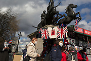 On the day that Chancellor of the Exchequer Rishi Sunak unveiled a £30bn package to boost the economy and get the country through the coronavirus outbreak, some Asian visitors wearing face masks walk beneath Boucicca's statue on Westminster Bridge where a tourism trinket stall sells Union Jack flags and t-shirts, on 11th March 2020, in London, England.
