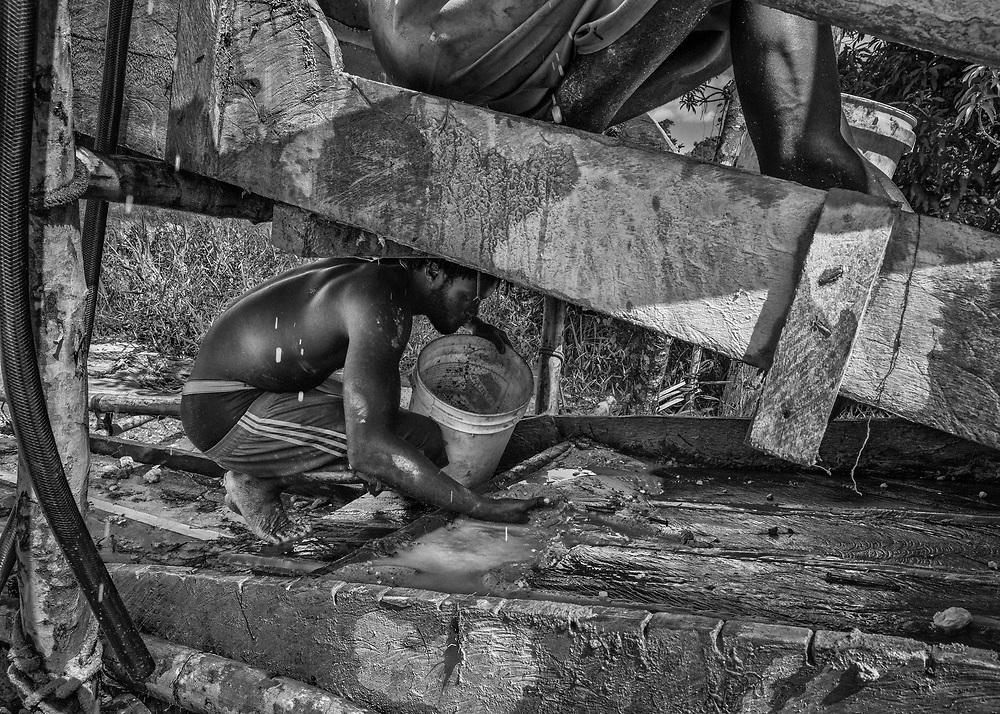 Rive Surinamaise du Maroni, 2015.<br /> <br /> Table d'orpaillage sur un site sauvage surinamais. La pression exercée par l'armée française pour juguler l'orpaillage clandestin dans l'Ouest du territoire guyanais amène la population locale à se tourner de nouveau de l'autre côté du fleuve. Or saisi, matériel brûlé, ravitaillement des sites plus difficile et coûteux à organiser, certains préfèrent alors traverser le Maroni pour venir travailler comme « frontaliers » sur les chantiers surinamais limitrophes.