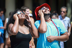 August 21, 2017 - Florida, U.S. - Ashely Tavarez and Amado Morillo of West Palm Beach observe the eclipse at CityPlace in West Palm Beach Monday, August 21, 2017. (Credit Image: © Bruce R. Bennett/The Palm Beach Post via ZUMA Wire)