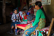 Kalpana Tamang (40), speaks with her younger daughter Binita (10) as they sit on their shared bed in their temporary shelter in Kavre, Bagmati, Nepal on 30 June 2015.  Kalpana, a widow with 3 children, has been supported by SOS Children's Villages for many years now and had receive the Home-in-a-Box after the earthquake destroyed her house, almost killing her two daughters. She now lives in a temporary shelter, sharing her dwelling with farm animals, and is trying to make ends meet by weaving bamboo baskets to supplement the financial assistance provided by SOS Childrens Villages. The NGO mostly supports her children's welfare and schooling as well as provides her with essential household and schooling items like kitchen utensils and school books and uniforms. Photo by Suzanne Lee for SOS Children's Villages