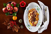 Roasted pork fillet with apples on white plate, typical fall-winter recipe. Photographed from above.
