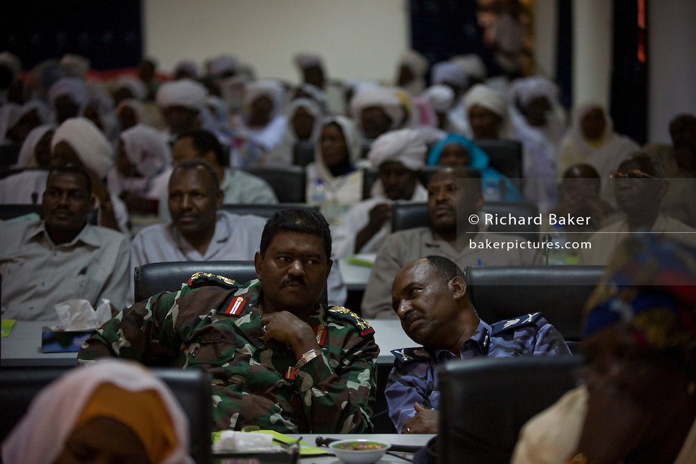 An army officer and police chief listen to speeches and opinions given by ladies attending the first-ever international Conference on Womens' Challenge in Darfur, gather in a compound belonging to the Govenor of North Darfur in Al Fasher (also spelled, Al-Fashir) where the women from remote parts of Sudan gathered to discuss peace and political issues.