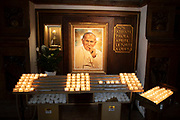 Interior with candles and portrait of Pope John Paul II in the Cathedral of San Rufino in Assisi, Umbria, Italy. Pope John Paul II served as Pope and sovereign of the Vatican City State from 1978 to 2005. He is called Saint John Paul the Great by some Catholics. In this church Saint Francis of Assisi, Saint Clare, and many of their original disciples were baptised. Assisi is a town in the Province of Perugia in the Umbria region, on the western flank of Monte Subasio. It is generally regarded as the birthplace of the Latin poet Propertius, and is the birthplace of St. Francis, who founded the Franciscan religious order in the town in 1208, and St. Clare, Chiara dOffreducci, the founder of the Poor Sisters, which later became the Order of Poor Clares after her death. Assisi is now a major tourist destination for those sightseeing or for more religious reasons.