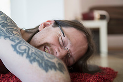 Tattooed man with closed eyes relaxing on carpet at home