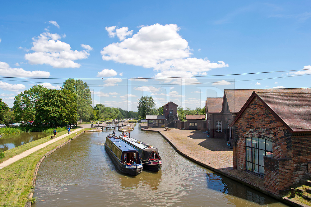 """© Licensed to London News Pictures. 22/06/2019. Hatton, Warwickshire, UK. Narrowboats pass the Canal and River Trust as they ascend the Hatton Flight, or """"stairway to heaven"""", a flight of 21 locks on the Grand Union Canal during a hot summers day Warwickshire. Photo credit: LNP"""
