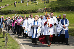 © Licensed to London News Pictures. 05/05/2016. Tissington, UK. Members of the church lead a procession of people to bless the six dressed wells in the Derbyshire village of Tissington. The origins of well dressing may have pagan roots later given a Christian Meaning. The dressings are made of clay dug locally which is adorned with dried flowers. The dressings are erected on the eve of Ascension day ready for the ceremony of blessing. Photo credit : Ian Hinchliffe/LNP