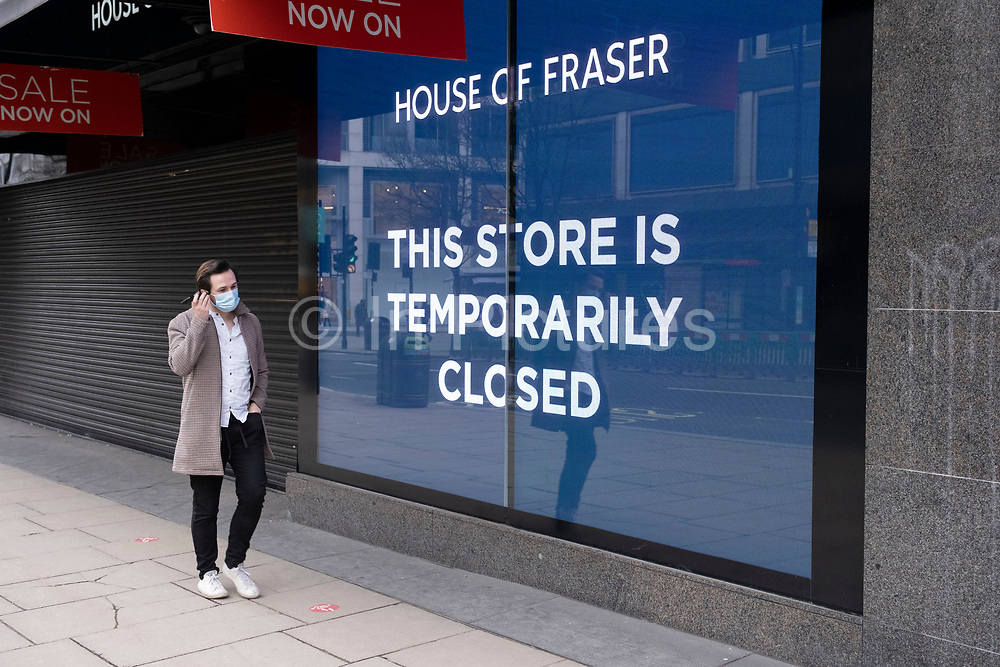 Man on Oxford Street wearing face masks passes the temporarily closed House of Fraser department store as the national coronavirus lockdown three continues on 4th March 2021 in London, United Kingdom. With the roadmap for coming out of the lockdown has been laid out, this nationwide lockdown continues to advise all citizens to follow the message to stay at home, protect the NHS and save lives.
