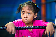 """18 DECEMBER 2104 - BANGKOK, THAILAND: A girl who wants to box watches a sparring session at the Kanisorn gym. The Kanisorn boxing gym is a small gym along the Wong Wian Yai - Samut Sakhon train tracks. Young people from the nearby communities come to the gym to learn Thai boxing. Muay Thai (Muai Thai) is a Thai fighting sport that uses stand-up striking along with various clinching techniques. It is sometimes known as """"the art of eight limbs"""" because it is characterized by the combined use of fists, elbows, knees, shins, being associated with a good physical preparation that makes a full-contact fighter very efficient. Muay Thai became widespread internationally in the twentieth century, when practitioners defeated notable practitioners of other martial arts. A professional league is governed by the World Muay Thai Council. Muay Thai is frequently seen as a way out of poverty for young Thais and Muay Thai camps and schools are frequently crowded. Muay Thai professionals and champions are often celebrities in Thailand.     PHOTO BY JACK KURTZ"""