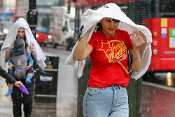 © Licensed to London News Pictures. 28/07/2021. London, UK. A woman is caught during a torrential downpour in north London. According to The Met Office, wet weather is expected in the capital for this week. Photo credit: Dinendra Haria/LNP