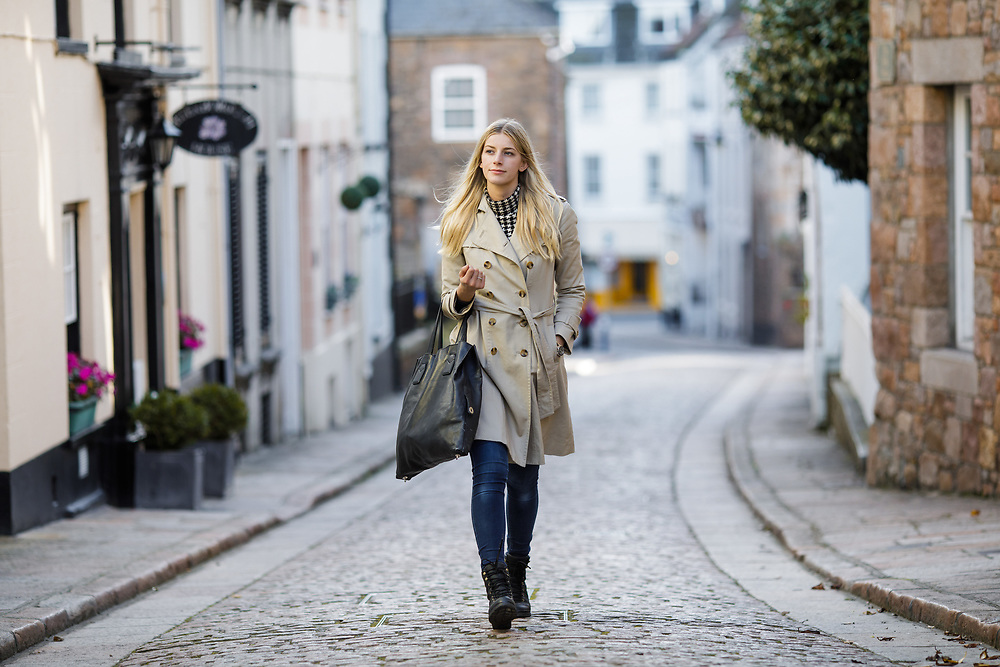Lady walking past apartments and housing along the quaint cobbled street of St Aubin, a popular tourist destination in Jersey, CI