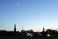 Goshen, New York - A crescent moon and Venus, at right, shine above church steeples at twilight on June 15, 2010.