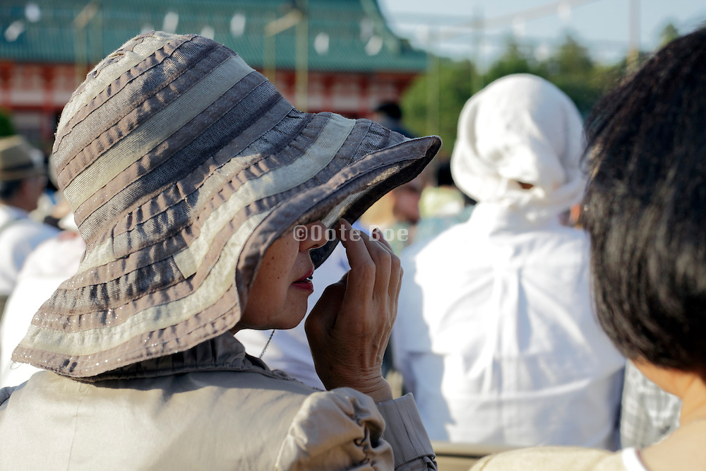 woman wearing a large brim fashionable hat to protect herself against the strong sun