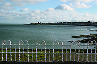 White railings and view from DunLaoghaire Pier looking towards Sandycove in Dublin Ireland
