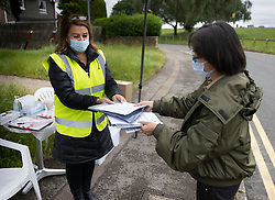 © Licensed to London News Pictures. 19/06/2021. Tattenham Corner, UK. A local resident is handed a home PCR covid-19 test at a mobile test centre at Tattenham Corner, Surrey. Surge testing for the coronavirus is taking place in parts of Surrey after a rise in infections caused by the delta variant. Photo credit: Peter Macdiarmid/LNP